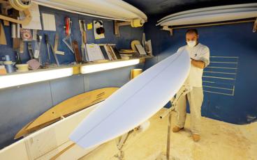 Erwan Bourhis, alias Juanito, dans son atelier de Mejou Roz, à proximité de la Torche, l'un des hauts lieux du surf français. On le voit ici finaliser le façonnage d'un pain de mousse. La fiche du client, où sont portées toutes les indications nécessaires pour réaliser cette planche, est fixée au porte-bloc posé sur l'étagère.