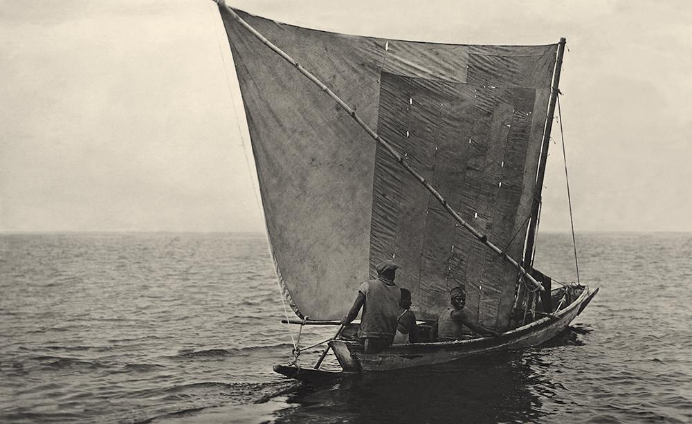 Pirogue de pêche photographiée au large de Dakar. Remarquer les deux écoutes –dont l'une capelée sur la livarde– et l'anneau dans lequel elles passent au niveau de l'éperon, ainsi que la pagaie qui sert de gouvernail.