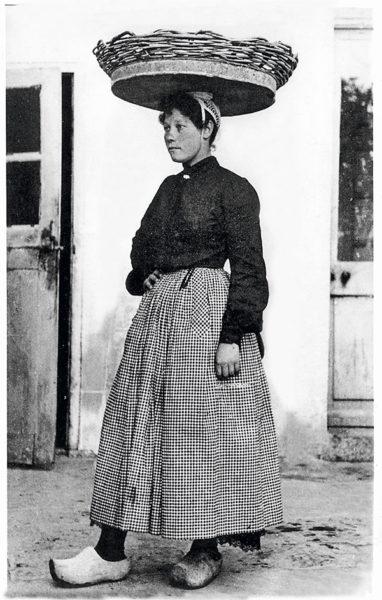 Femme portant un panier de sardines sur la tête.