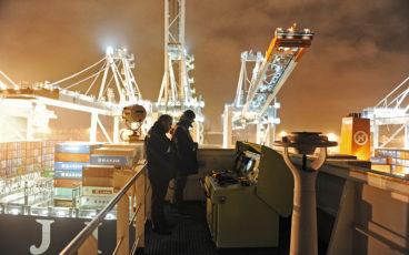 Deux techniciens en charge du déchargement d'un porte conteneurs