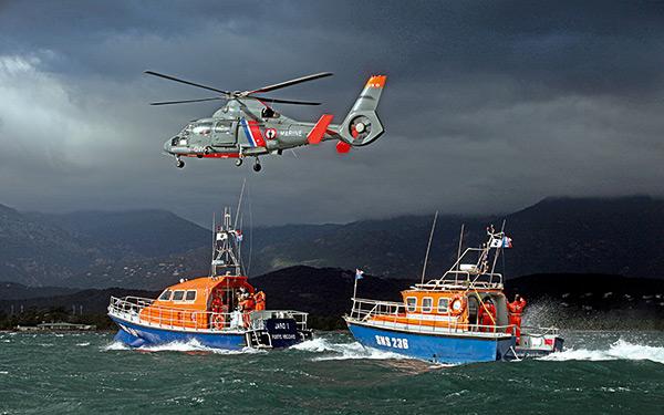 deux bateaux snsm et hélicoptère