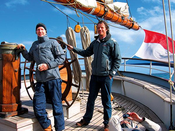 deux hommes à la barre d'un bateau