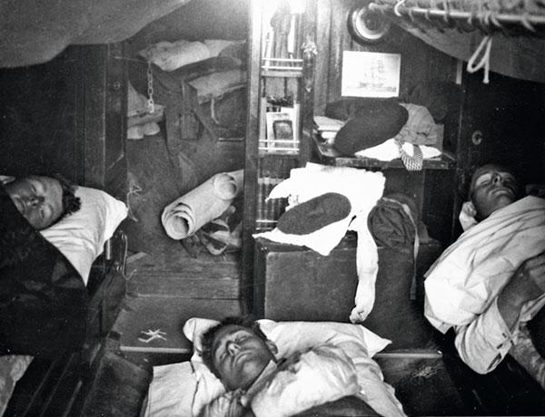hommes dormant dans les bannettes d'un bateau