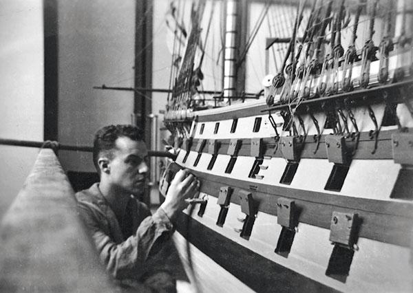 homme travaillant sur maquette navale