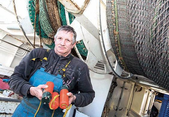 À bord du Carmalia, chalutier pélagique lorientais de 17,50mètres, travaillant en bœuf, un matelot présente les pingers, répulsifs acoustiques à dauphins, qui seront installés à l'entrée du chalut.