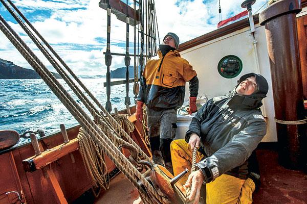 Le capitaine Maarten de Jong règle la grand-voile, sous l'œil d'un matelot, Ben Bolt, dans le canal de Beagle.